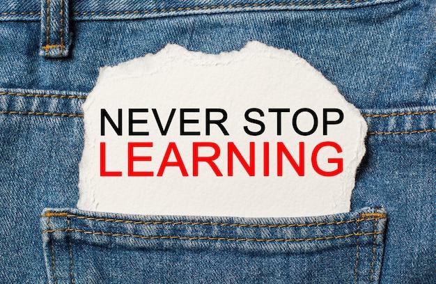 Non smettere mai di imparare su sfondo di carta strappata sullo studio dei jeans e sul concetto di istruzione