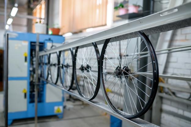 Nuove ruote di bicicletta in alluminio in catena di montaggio, nessuno. parti della bici in fabbrica, cerchi con mozzi e raggi sulla macchina, tecnologia moderna
