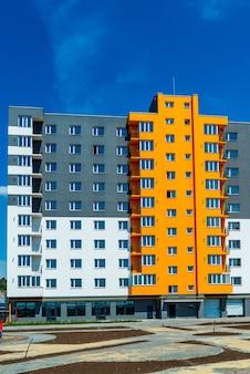 Nuovo blocco di appartamenti moderni con balconi e cielo blu sullo sfondo