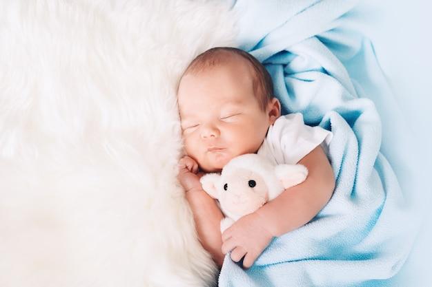 Neonato bambino di una settimana che dorme pacificamente con un simpatico peluche nella culla in uno sfondo di stoffa
