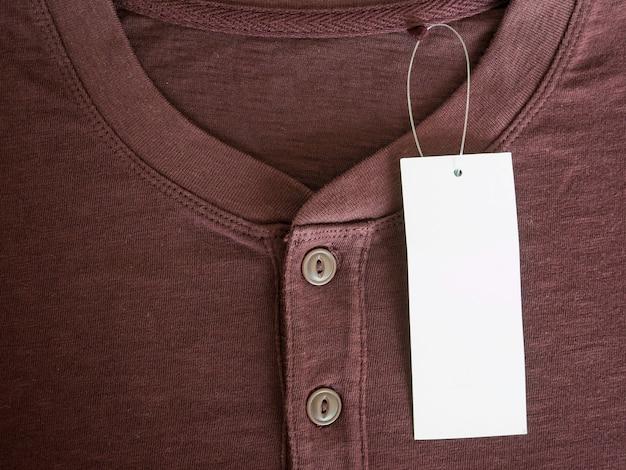 Nuova camicia marrone con cartellino del prezzo in bianco