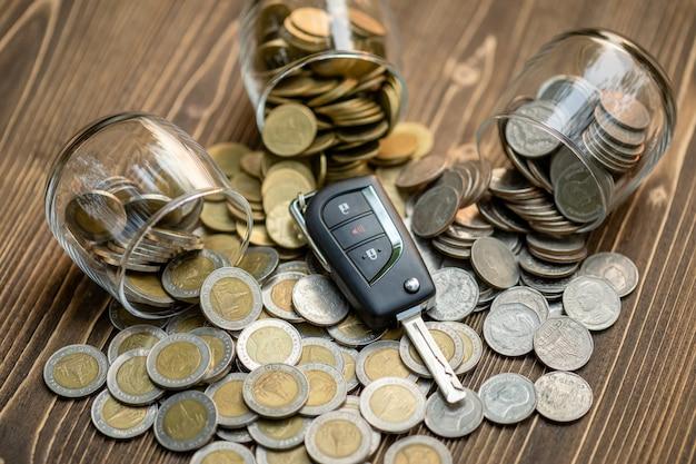Mucchio di chiavi della nuova auto della moneta sulla tavola di legno. auto finanziaria, acquisto auto o concetto di noleggio auto