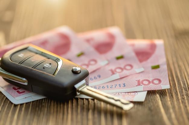 Nuove chiavi della macchina con banconota cinese sul tavolo di legno. acquisto di auto o concetto di noleggio auto