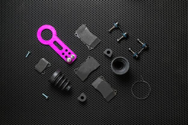Un nuovo piatto di raccolta di pezzi di ricambio per auto giaceva su sfondo scuro, servizio di modifica dei dettagli