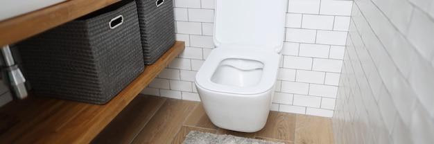 Nuova toilette bianca in ceramica contro il primo piano della parete leggera
