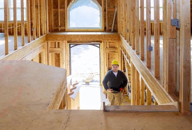 Costruttore di casa della nuova costruzione in casco che cammina sul pc della compressa della tenuta