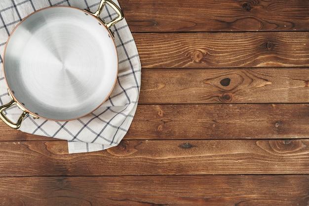 Nuova pentola in rame su tavolo in legno vista dall'alto