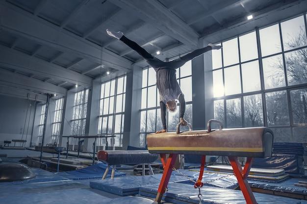 Nuovo giorno. piccolo ginnasta maschio che si allena in palestra, flessibile e attivo. ragazzino caucasico, atleta in abbigliamento sportivo che si esercita in esercizi di forza, equilibrio. movimento, azione, movimento, concetto dinamico.