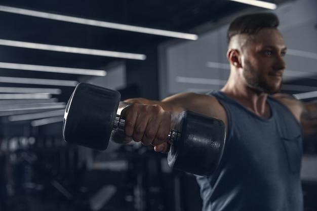 Nuovo giorno per il potere. giovane atleta caucasico muscolare che si esercita in palestra con i pesi. uomo che fa esercizi di forza, allenando la parte superiore del corpo. fitness, benessere, stile di vita sano, concetto di bodybuilding.
