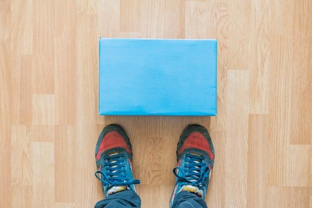 Il nuovo pacco consegnato giaceva davanti alle gambe al chiuso sul pavimento f