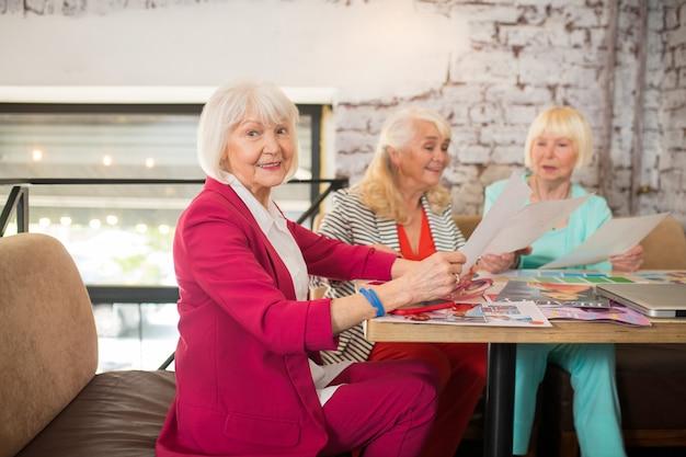 Nuovi vestiti. tre signore anziane ben vestite che discutono di una nuova collezione di abiti