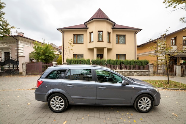 Nuova costosa macchina grigia parcheggiata in un parcheggio pavimentato davanti al grande cottage a due piani