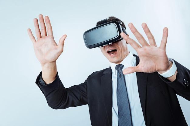 Nuova esperienza. lavoratore stupito che gesticola mentre indossa un auricolare per realtà virtuale e gioca ai videogiochi dopo lunghe ore di lavoro in ufficio.