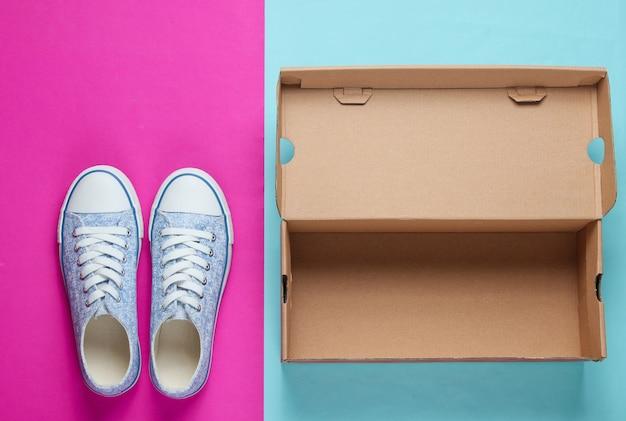 Nuove sneaker alla moda e scatola di cartone vuota sulla superficie della carta colorata.