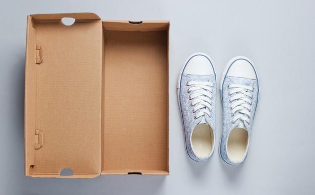 Nuove sneaker alla moda e scatola di cartone vuota su superficie grigia.