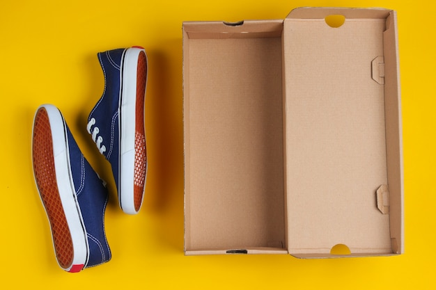 Nuove sneaker alla moda e scatola di cartone vuota su superficie gialla.