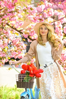 Nuova vita verde. sakura in fiore rosa. rilassarsi nel parco. moda e bellezza. donna giro in bicicletta d'epoca. ragazza romantica sotto il fiore di sakura. bella stagione primaverile natura. fiori di ciliegio che sbocciano.