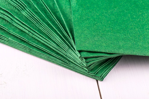 Nuovi tovaglioli verdi su un tavolo da pranzo in legno bianco