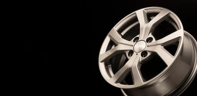 Nuovo cerchio in lega grigio argento su sfondo nero.