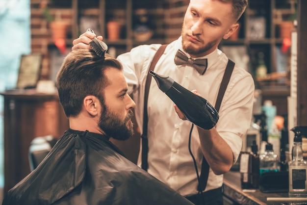 Nuovo taglio di capelli. vista laterale del giovane uomo barbuto che si fa pettinare dal parrucchiere con l'asciugacapelli