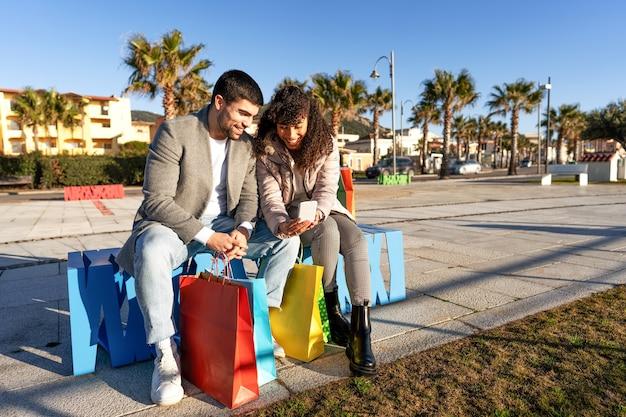 Nuove abitudini umane con le tecnologie mobili: giovani coppie felici che si siedono all'aperto su una panchina della città divertendosi usando lo smartphone