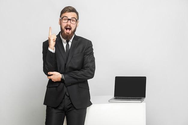 Nuova idea! ritratto di bello sorpreso barbuto giovane uomo d'affari in abito nero sono in piedi vicino al suo posto di lavoro e mostrando il dito con la bocca aperta. isolato, girato in studio, indoor, sfondo grigio
