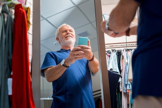 Nuova immagine. mezzo busto di gioioso uomo dai capelli grigi utilizzando il telefono cellulare e facendo selfie davanti allo specchio mentre si ammira il suo riflesso