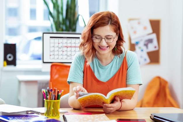 Nuova informazione. felice giovane donna che legge un libro mentre impara nuove informazioni