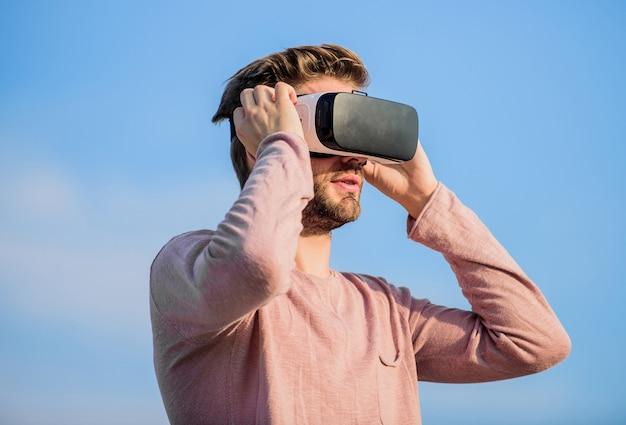 Nuove innovazioni. l'uomo indossa occhiali vr wireless... occhiali vr sfondo cielo uomo sexy. creare un proprio business. futuro digitale e innovazione. realtà maschile. tecnologia del futuro. ragazzo occhiali per realtà virtuale.