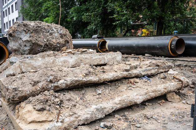 Nuovi tubi dell'acqua nera isolati e lastre di cemento sulla strada della città in giornata estiva. concetto di infrastruttura fognaria urbana, ammodernamento e ricostruzione del sistema sotterraneo.
