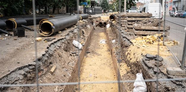 Nuove tubazioni isolate dell'acqua nera e lastre di cemento sulla strada della città nel giorno d'estate