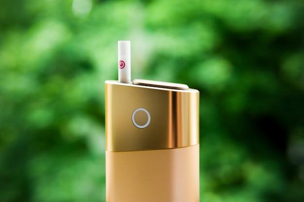 Un nuovo tipo di sigaretta elettronica. sistema di riscaldamento del tabacco iqos. mod per il fumo sta con una sigaretta. sigarette riscaldate per fumare. forma sicura di fumo.