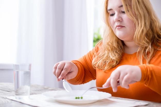 Nuovo stile di vita. determinata donna in sovrappeso seduta al tavolo e mangiare piselli