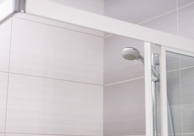 Nuovo moderno soffione doccia su parete piastrellata in cabina doccia con porte in vetro trasparente in bagno