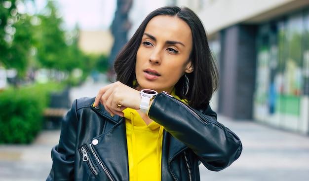 Nuove tecnologie moderne! giovane imprenditrice per strada, che possiede uno smartwatch, smartphone, cuffie wireless.