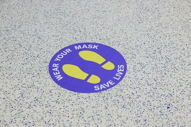 Nuova normalità dopo la pandemia di coronavirus, scritta covid-19 sul pavimento: indossa la maschera, salva vite