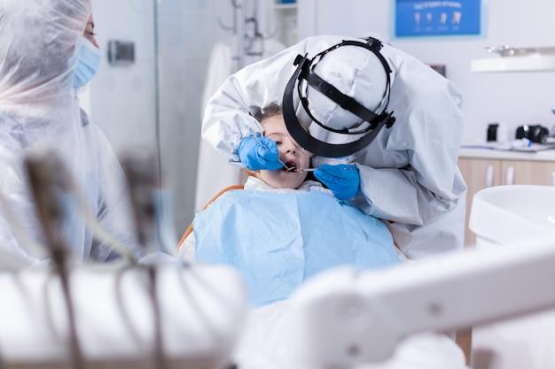 Nuova normalità in studio dentistico in corso di visita odontoiatrica per bambina con pettorina. dentista in tuta da coronavirus che utilizza uno specchio curvo durante l'esame dei denti del bambino.