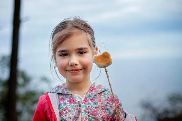 Nuova normale fase di fuga, passeggiate nella natura selvaggia e attività ricreative all'aperto in famiglia. bambini che cucinano e degustano marshmallow fritti sul fuoco, escursione nel fine settimana, stile di vita
