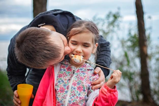 Nuova normale fase di fuga, passeggiate nella natura selvaggia e attività ricreative all'aperto in famiglia. bambini in piedi accanto al fuoco e cucinare marshmallow, escursioni nel fine settimana, stile di vita