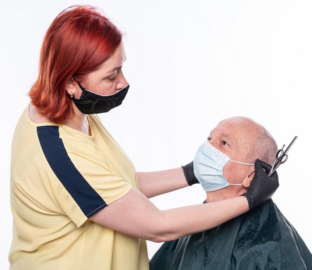 Nuovo concetto di taglio di capelli normale. parrucchiere donna che taglia i capelli a un uomo anziano in maschera