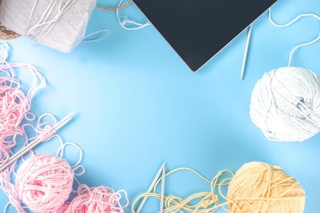 Nuova normale attività di hobby, impara a lavorare a maglia online classe di maglieria online. corso di maglieria online, vista dall'alto su sfondo blu copia spazio per il testo