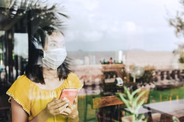 Nuovo concetto di persone con uno stile di vita normale, donna asiatica viaggiatore felice con maschera utilizzando il telefono cellulare nel caffè della caffetteria a causa dello scoppio del coronavirus covid-19 in thailandia