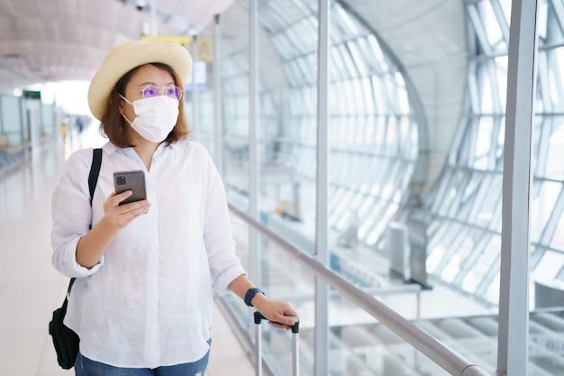 Il nuovo turista normale che indossa la maschera facciale sta viaggiando in aeroporto, il nuovo stile di vita viaggia dopo il covid-19. sistema sanitario di distanza sociale, sicurezza e concetto di bolla di viaggio.