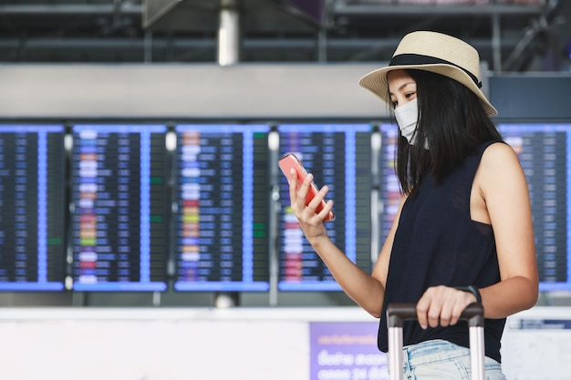 Donna asiatica del nuovo viaggiatore normale con maschera e bagagli utilizzando il telefono cellulare in aeroporto terminale thailandia