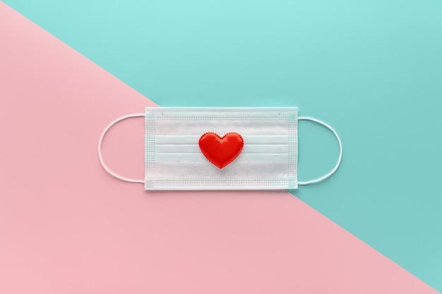 Nuovo normale concetto di san valentino. maschera medica decorata con cuore rosso su rosa pastello e ciano