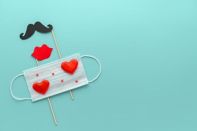 Nuovo normale concetto di san valentino. maschera medica decorata con cuori rossi e baffi di carta