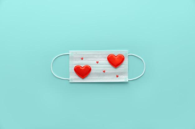 Nuovo normale concetto di san valentino. maschera medica decorata con cuori rossi su ciano pastello