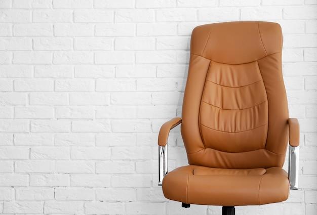 Nuova sedia da ufficio sul muro di mattoni