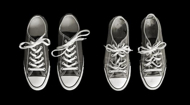 Nuove e vecchie scarpe da ginnastica generiche isolate sul nero