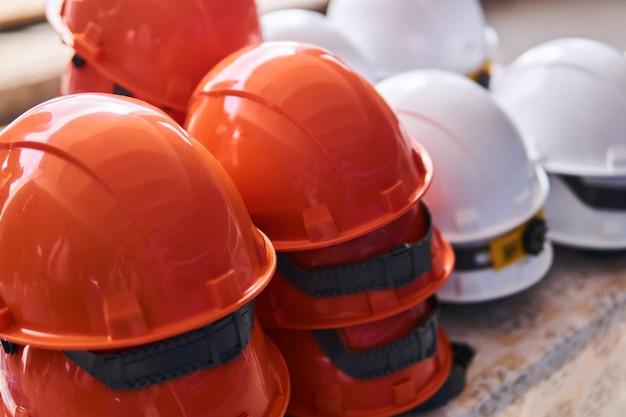 Nuovi caschi industriali arancioni e bianchi da vicino